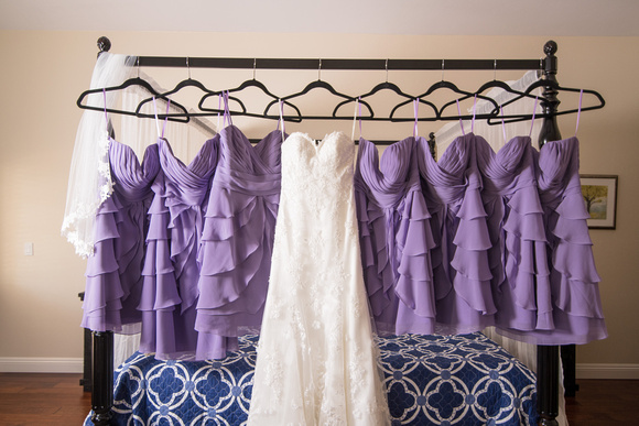 Wedding dress and bridesmaid dresses hanging on bed frame