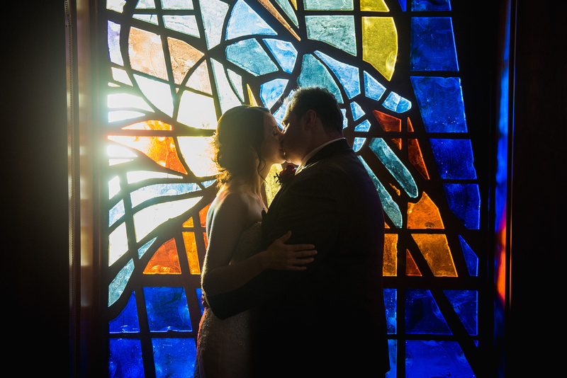 Bride and groom kiss in front of a stained glass window at rancho bernardo community presbyterian church.