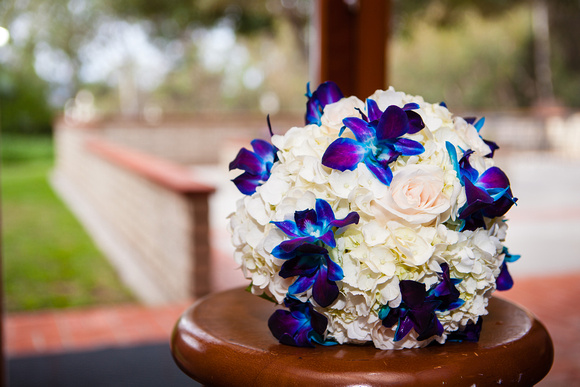A white rose wedding bouquet with blue and purple orchids peeking through.