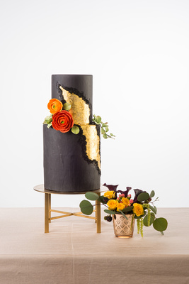 Simple but chic black geode cake with sugar flower details and shiny gold by Sweet Cheeks Baking Company.