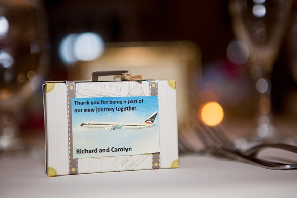Suitcase travel wedding favor as part of a wedding table setting.