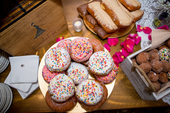 Yummy frosted donuts, including cake, maple bars, and donut holes from Peterson's Donut Corner on the dessert table.