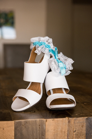 Bridal shoes and garter with light blue ribbon on table