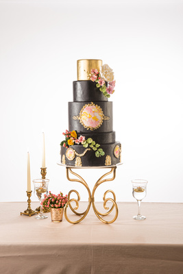 Black luxury wedding cake with gold and flower accents by sweet cheeks baking company.