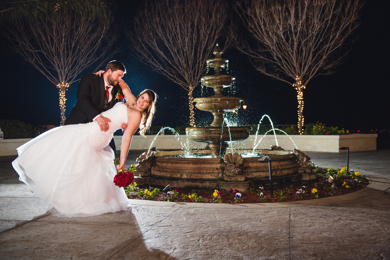 Bride and groom with red roses dipping and kissing in front of a greenery arch at Wedgewood Fallbrook in Fallrook, CA.