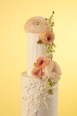 Beautful floral wedding cake with icing decor and real flowers by Laura Marie's Cakes in San Diego, CA.