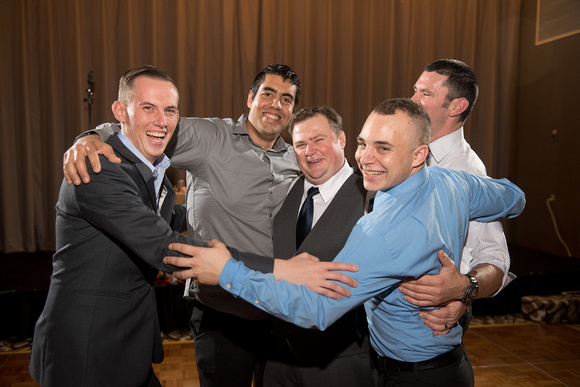The groom and some friends share a group hug.