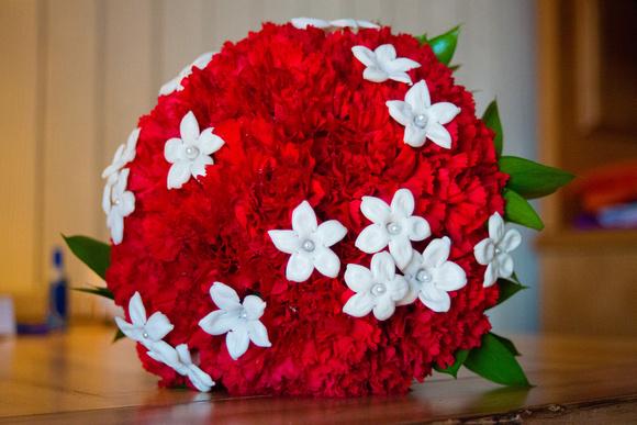 Red carnation wedding bouquet with stephanotis Madagascar jasmine flowers and pearl picks.