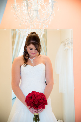 Bride Elizabeth with her bouquet of red roses made by Lovely Stems Floral of Oceanside, CA in the bridal room of Wedgewood Fallbrook.