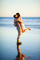 A woman in a dress jumping into the arms of a young man dressed in army fatigues agains a background of the ocean and sky near the Hotel Del Coronado.