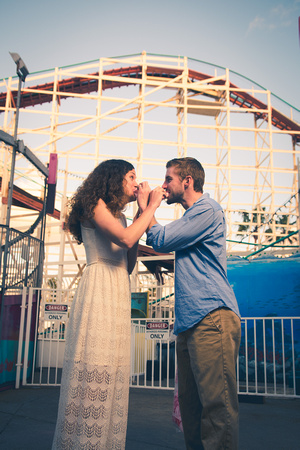 An engagement couple feeds each other fair food in front of the Giant dipper roller coaster at Belmont Park in Mission Beach, San Diego, California.