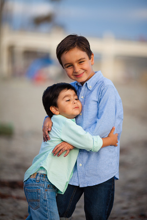 Two young dark haired boys giving each other a hug on the beach in Oceanside, California.