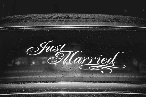 """Vintage getaway car with """"just married"""" sticker."""