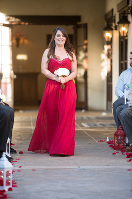 Bridesmaid walks down the aisle in classic red gown at Wedgewood Fallbrook.