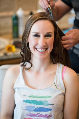 Smiling bride getting her hair and makeup done