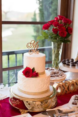 Classic white wedding cake with crystals, red roses, and decorative gold topper made by BoCakes Bakery.
