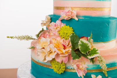 Detail shot with flowers of hand painted wedding cake by Flour Power Bakery in San Diego, CA.