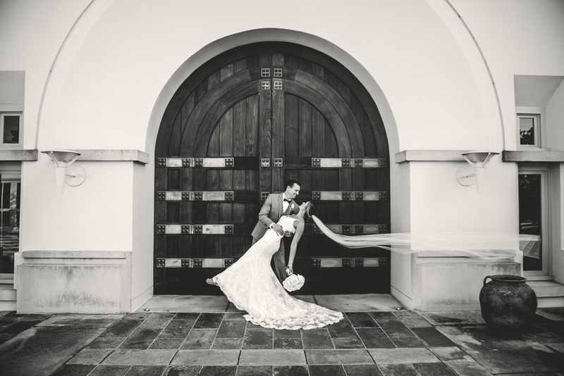 Bride and Groom in front of wooden church door with veil flying in the wind