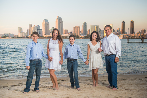 A family of five holding hands on a coronado beach with a view of the san diego skyline behind them.